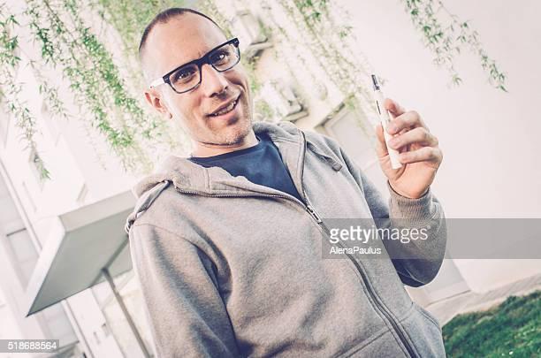 vaping im Freien Mann, die Verwendung von elektronischen Zigaretten im täglichen Leben