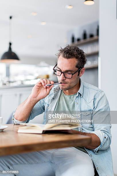 man vaping ( e-cigarette ) while reading a book