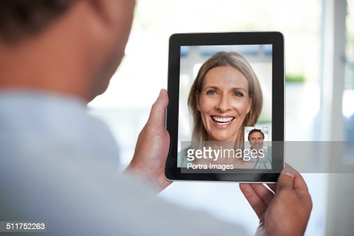 Man video chatting with woman on tablet PC