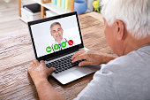 Senior Man Video Conferencing With Doctor On Laptop Over Wooden Desk