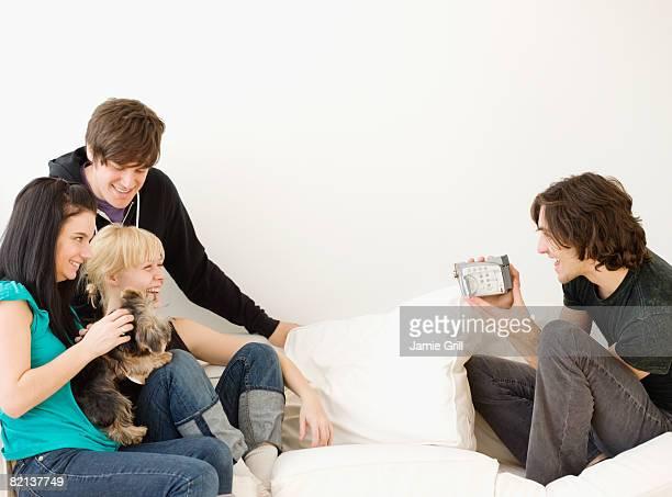 Man video recording friends on sofa