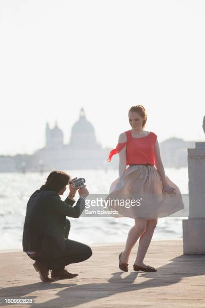 Homme videoing femme souriante au bord de l'eau à Venise