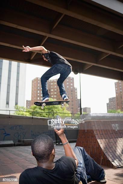 Man videotaping midair skateboarder