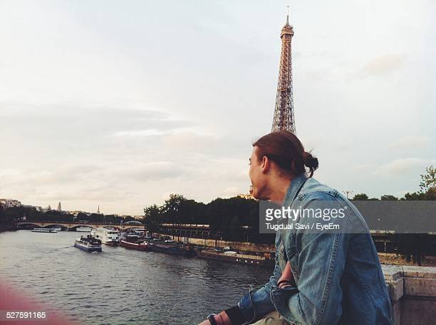 Man Viewing River Against Eiffel Tower