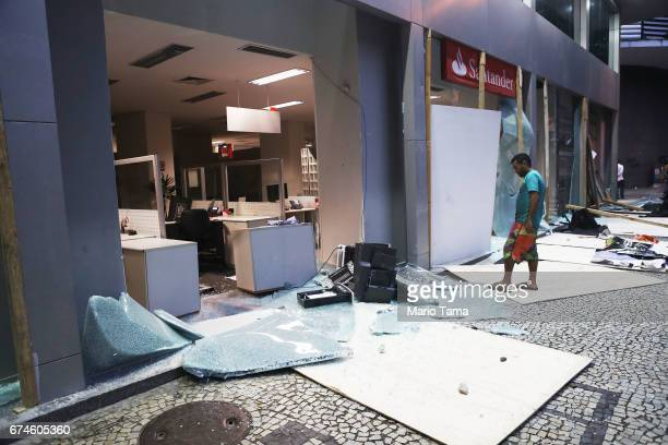 A man views a bank damaged by protestors during a nationwide general strike on April 28 2017 in Rio de Janeiro Brazil The general strike was...