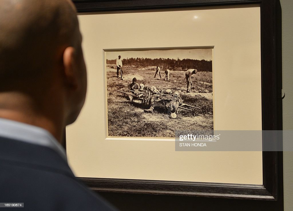 A man views 'A Burial Party, Cold Harbor, Virginia, April 1865', albumen silver print from glass negative by John Reekie in the exhibition, 'Photography and the American Civil War' April 1, 2013 at The Metropolitan Museum of Art in New York. AFP PHOTO/Stan HONDA
