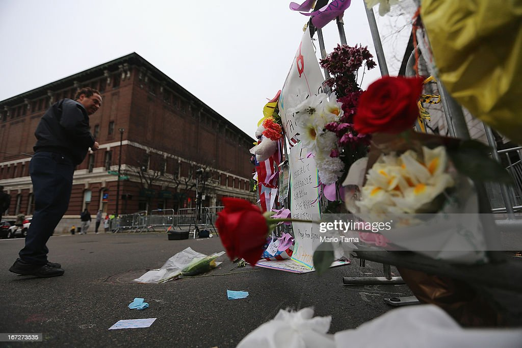 A man views a makeshift memorial at a barricade blocking a still closed section of Boylston Street near the site of the Boston Marathon bombings on April 23, 2013 in Boston, Massachusetts. Business owners and residents of the closed section were allowed to return to their properties today while under escort of city staff.