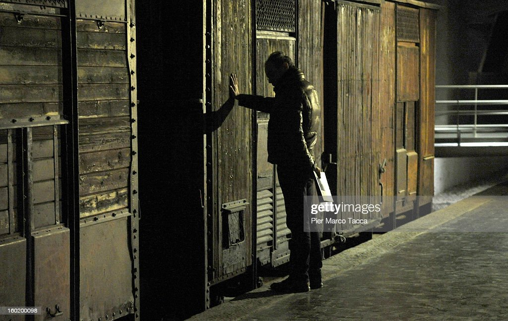 A man views a train carriage, part of a memorial at Platform 21 (Binario 21), which was used for transporting Jews to concentration camps during World War II, during the opening of 'Memoriale della Shoa' on International Holocaust Remembrance Day on January 27, 2013 in Milan, Italy. 'Memoriale della Shoa' is located at Platform 21 (Binario 21), which formed part of a secret underground rail network that transported hundreds of Jews to camps such as Auschwitz and Dachau, from1943 to 1945.