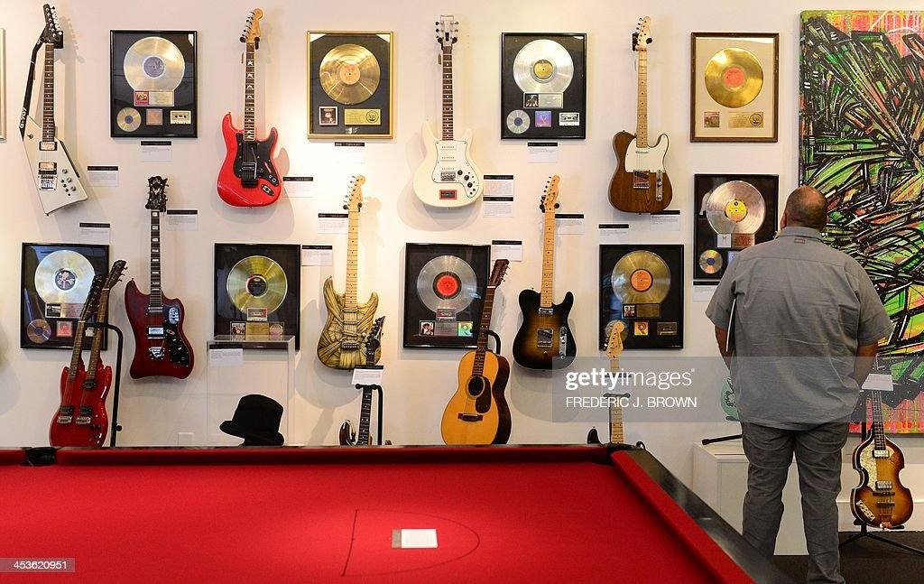 A man views a wall of guitars belonging to rock stars beside the Rolling Stones Red Snooker Table displayed amid preparations at Julien's Auction House in Beverly Hills, California, on December 4, 2013, where two highly anticipated auctions, the Street Art Auction and Icons and idols: Rock and Roll, will take place over the course of three days begnning December 5th. The snooker table is estimated between US$10,000-20,000. AFP PHOTO / Frederic J. Brown == RESTRICTED