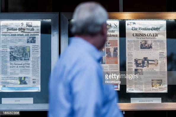 A man views front pages of newspapers displayed in front of the Newseum in Washington DC US on Thursday Oct 17 2013 The passage last night by wide...