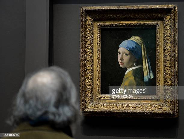 A man views 'Girl with a Pearl Earring ' by Johannes Vermeer in the exhibition 'Vermeer Rembrandt and Hals Masterpieces of Dutch Painting from the...
