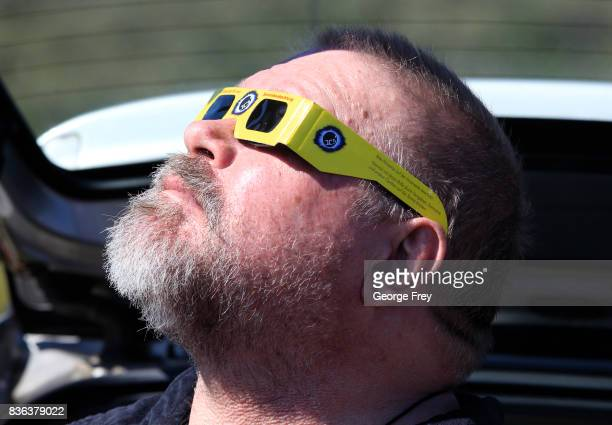 A man views the solar eclipse in the first phase of a total eclipse in Grand Teton National Park on August 21 2017 outside Jackson Wyoming Thousands...