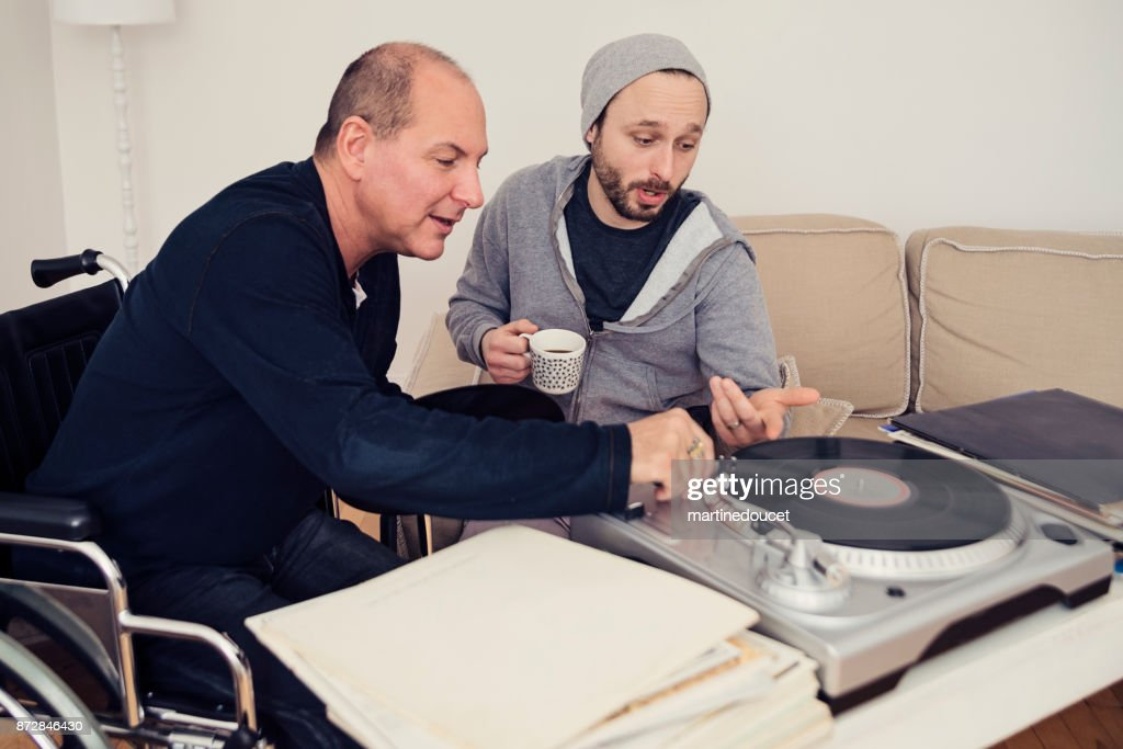 Man visiting a temporary disabled friend enjoying vintage records. : Stock Photo