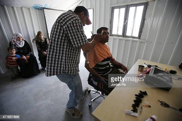 A man visits the barber shop that just opened as women wait with a child to get his hair cut in the new market in the AlAzraq camp for Syrian...