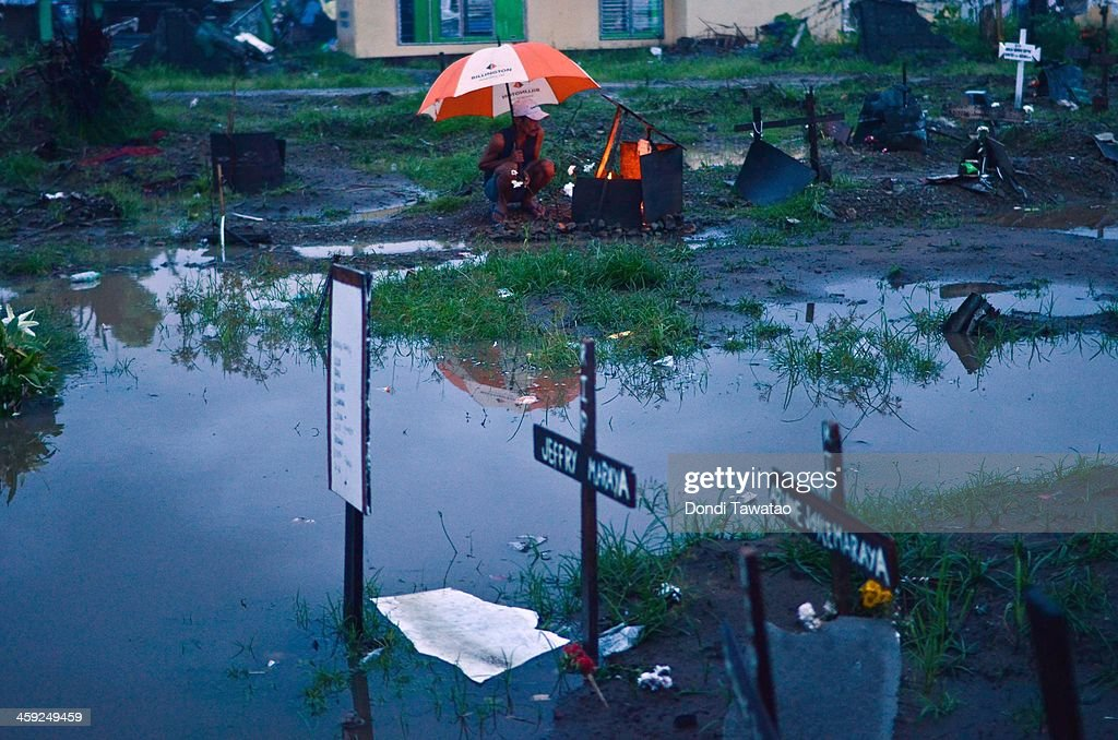 TACLOBAN LEYTE PHILIPPINES DECEMBER 24 A man visits the grave of a loved one who perished during the typhoon at a flooded mass grave on Christmas eve...