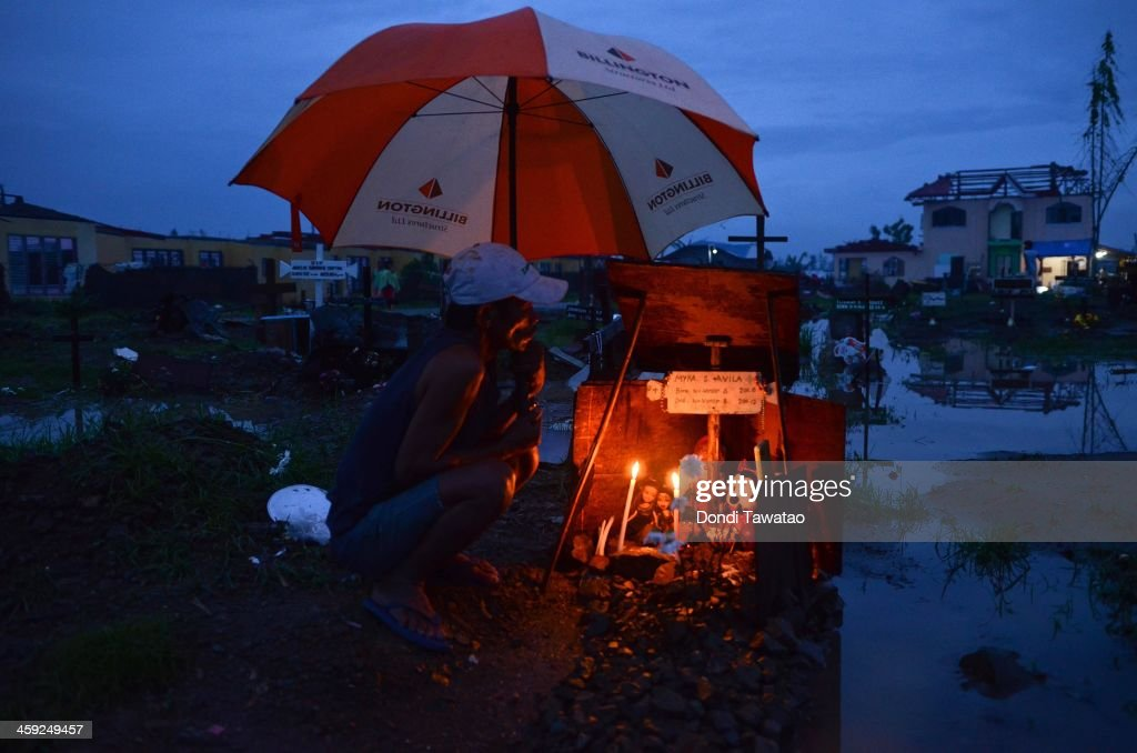 TACLOBAN LEYTE PHILIPPINES DECEMBER 24 A man visits the grave of a loved one who perished during Typhoon Haiyan at a flooded mass grave on Christmas...