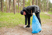 A man picking up the garbage and putting it in a blue garbage bag on a natural background. Ecology protection concept.