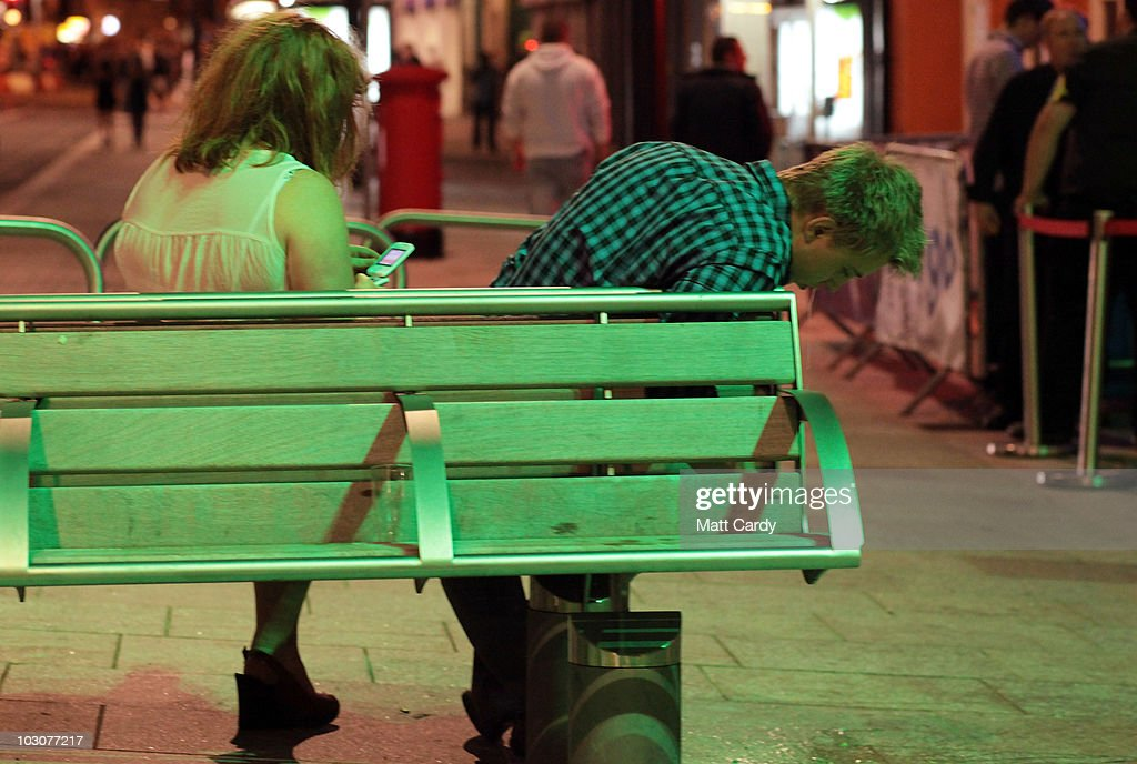 A man vomits as he sits with his girlfriend on a bench outside the various pubs and clubs in Cardiff city centre on July 24 2010 in Cardiff Wales The...