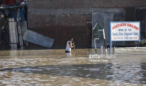 A man wades back through flood water to his home on a submerged road on September 11 2014 in Srinagar India Total of 130000 people have been rescued...