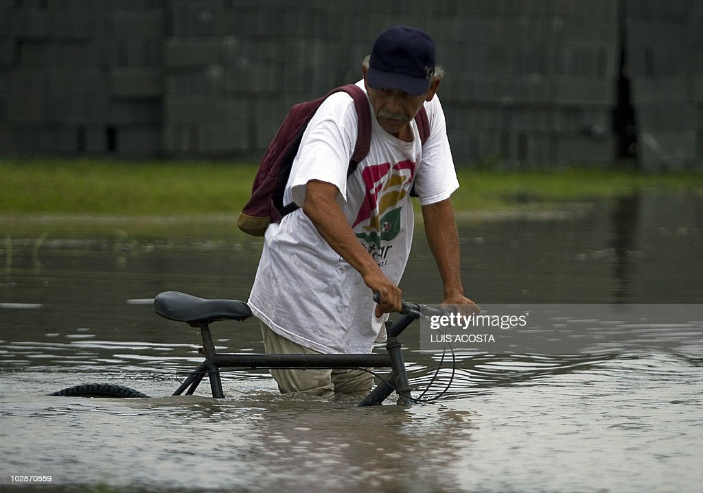 A man wades through a flooded street, after the passage of Hurricane Alex, in Matamoros, Tamaulipas State, on July 1, 2010. Alex, the first hurricane of the Atlantic season, weakened across northeast Mexico as it neared high mountains on Thursday, after disrupting oil clean-up operations in the Gulf of Mexico. Alex was downgraded to a tropical storm after roaring ashore late Wednesday as a Category Two hurricane slightly south of the eastern US-Mexico border. AFP PHOTO/Luis Acosta