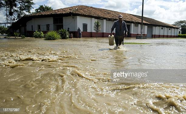 A man wades through a flooded street following the overflowing of the Cauca river on January 25 2012 in Candelaria department of Valle del Cauca...
