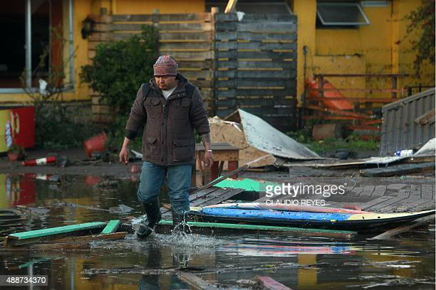 A man wades through a flooded street littered with debris in Concon some 110 km northwest of Santiago on September 17 2015 hit by an earthquake on...