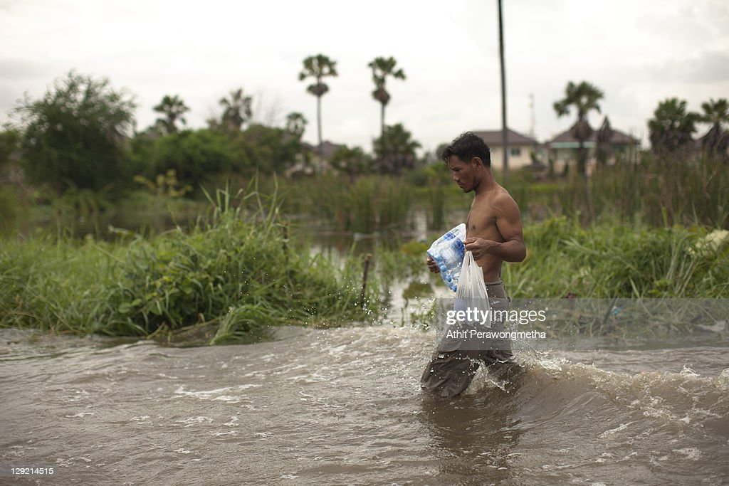 A man wades through floodwater on October 14, 2011 in Pathum Thani, north of Bangkok,Thailand. Crews of public workers, soldiers and volunteers are evacuating residents from flooded areas north of Bangkok as efforts continue to protect the capital from increased rainfall and rising tides during the worst floods to hit the country for decades.