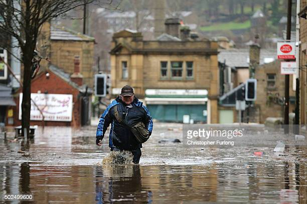 A man wades through floodwaters as rivers burst their banks on December 26 2015 in Hebden Bridge England There are more than 200 flood warnings...