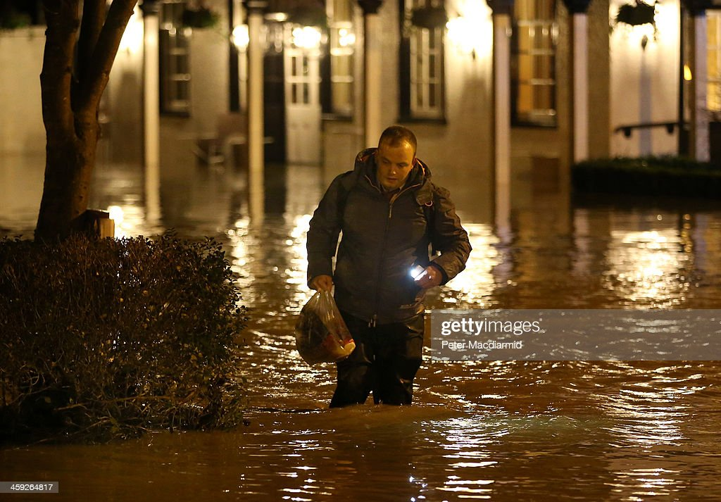 A man wades through rising floodwater from the River Mole outside the Burford Bridge Hotel on December 24, 2013 near Dorking, England. Christmas plans have been badly affected for thousands of people after storms across the UK have resulted in flooding, power cuts and significant problems with transport infrastructure.