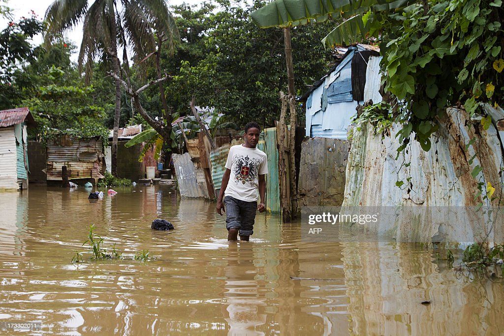 A man wades through the water in a flooded area of Santo Domingo, on July 11, 2013 after Tropical Storm Chantal lashed the impoverished Caribbean island of Hispaniola -- shared by Haiti and the Dominican Republic. A firefighter was killed and more than 6500 people were evacuated in the Dominican Republic as Chantal has now weaken into a 'tropical wave'. AFP PHOTO/Erika SANTELICES