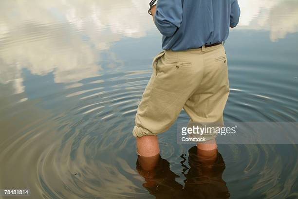 Man wading in pond