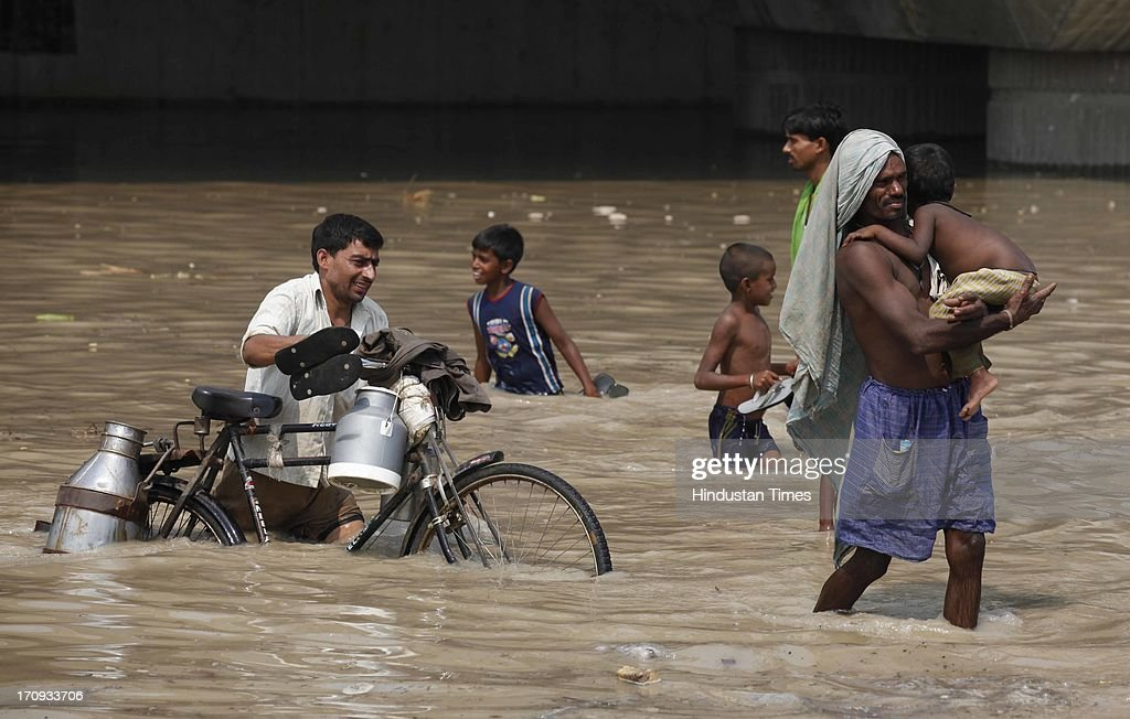 A man wading through submerged road near Yamuna Bank metro station during flood in river Yamuna on June 20, 2013 in New Delhi, India. Low-lying areas along the Yamuna remained submerged for the second consecutive day though the water level in the river started receding today.
