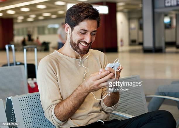 man waiting at airport, using smart phone