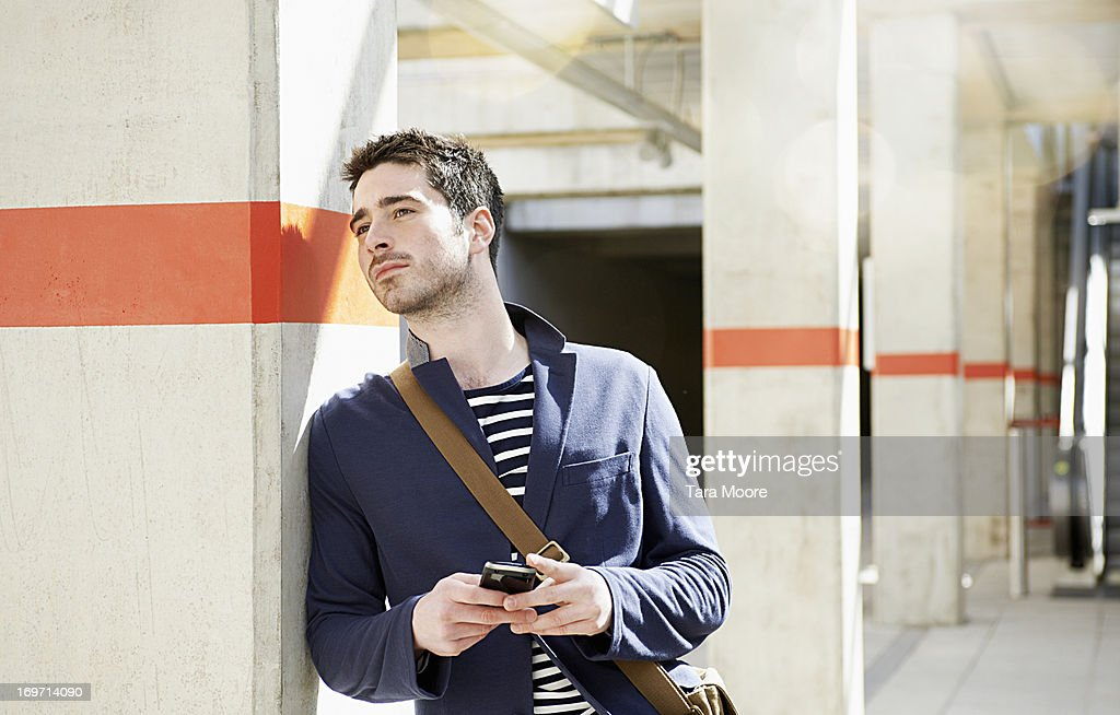 man waiting at train station holding mobile : Stock Photo