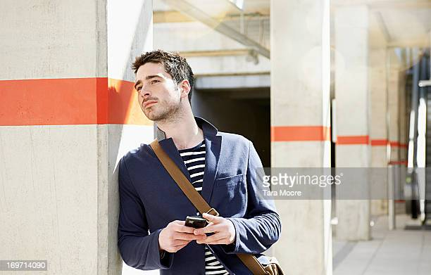 man waiting at train station holding mobile