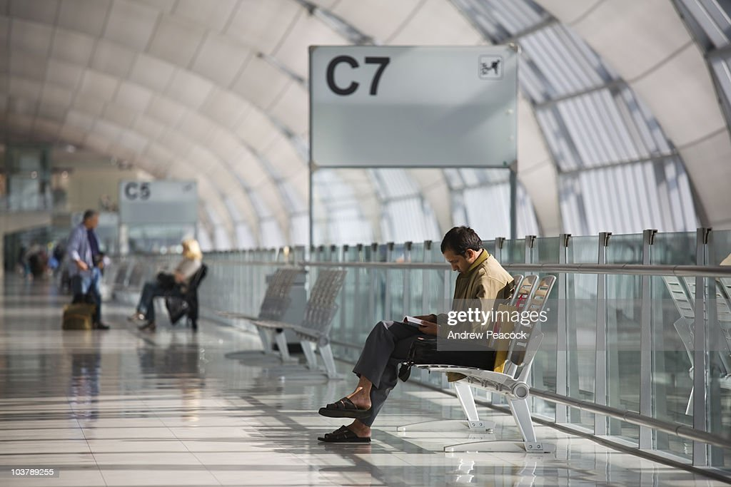 Man waiting for flight at gate at Suvarnabhumi International Airport, Bangkok.