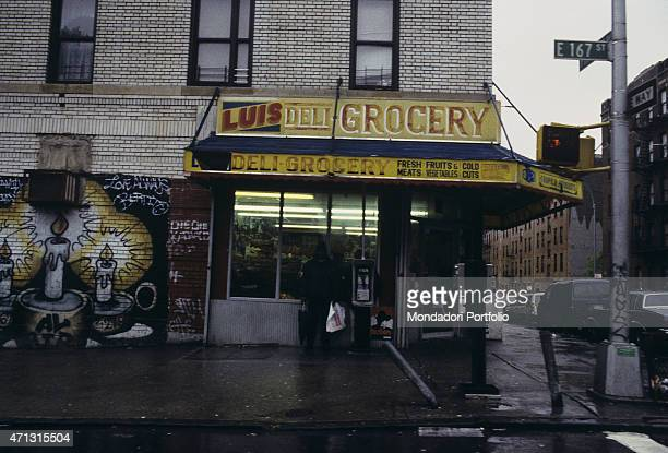 A man waiting for the rain ending under the canopy of a grocery in Bronx New York 1990s