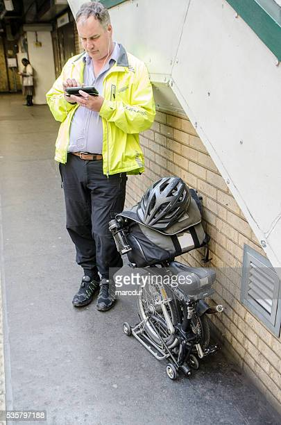 Man waiting in subway station with foldable bicycle