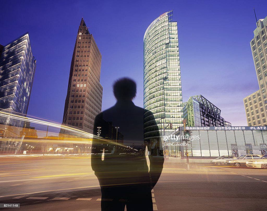 Man waiting to cross busy road with illuminated offices. : Stock Photo