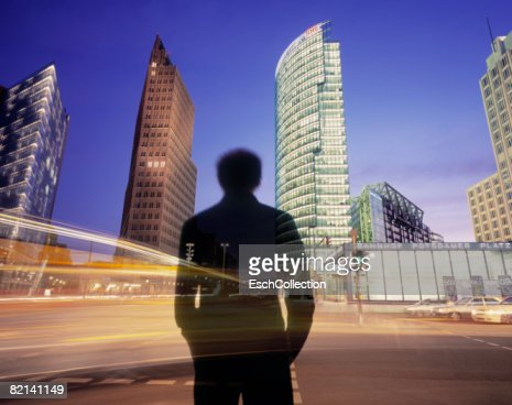 Man waiting to cross busy road with illuminated offices. : ストックフォト