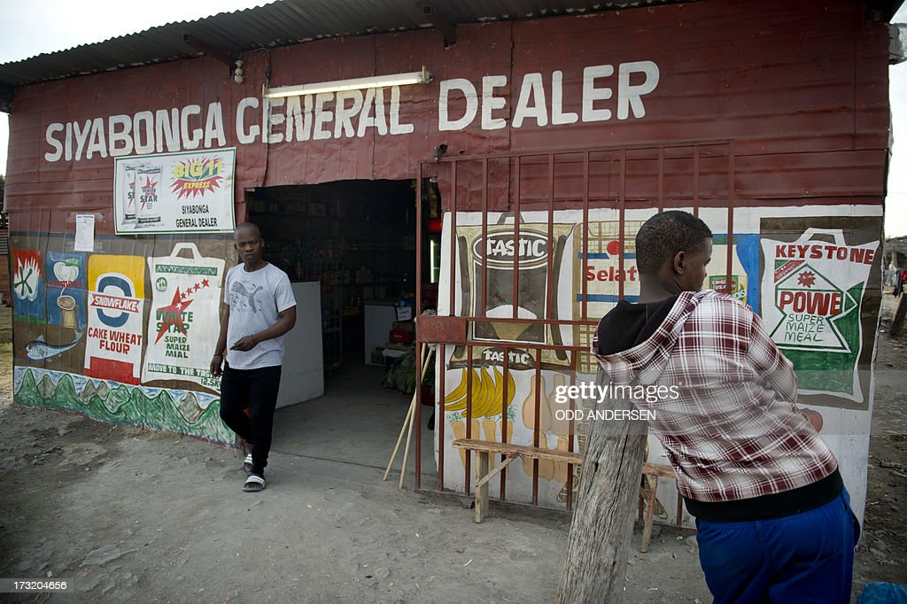 A man (R) waits as a customer leaves a general store on July 9, 2013 in the Nkaneng shantytown next to the platinum mine, run by British company Lonmin, in Marikana. On August 16, 2012, police at the Marikana mine open fire on striking workers, killing 34 and injuring 78, during a strike was for better wages and living conditions. Miners still live in dire conditions despite a small wage increase.