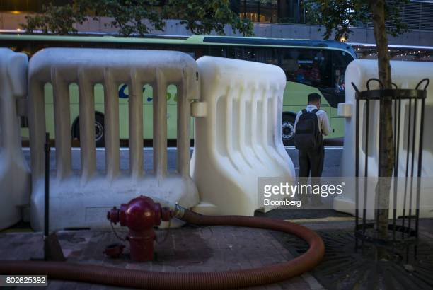 A man waits at a bus station next to water barricades near the Hong Kong Convention and Exhibition Center ahead of Chinese President Xi Jinping's...