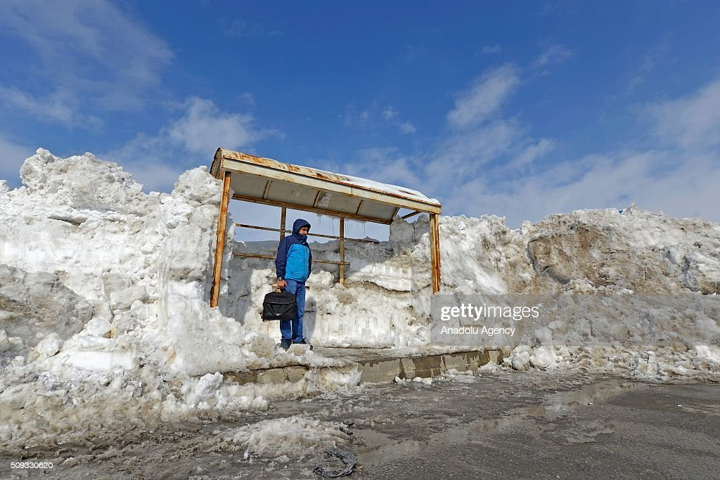 A man waits at a bus stop after a heavy snowfall, caused meters of snow depth on the ground in Turkey's Eastern city Bitlis on February 10, 2016. Snowfall covered road, bus stops, traffic signs as well as pavements.