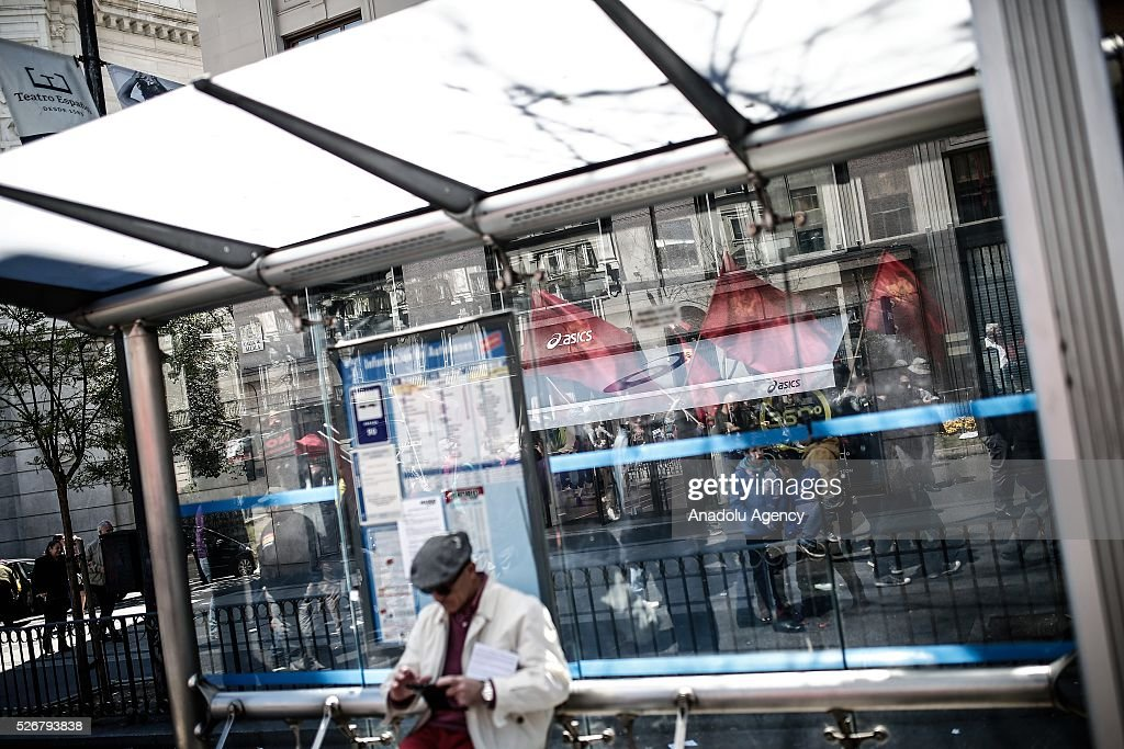 A man waits at a bus stop as workers, organized by labor unions and other labor organization take part in a rally to mark May Day, International Workers' Day in Madrid, Spain on May 01, 2016. Every year May Day is observed and commemorated as an official holiday all around Spain.
