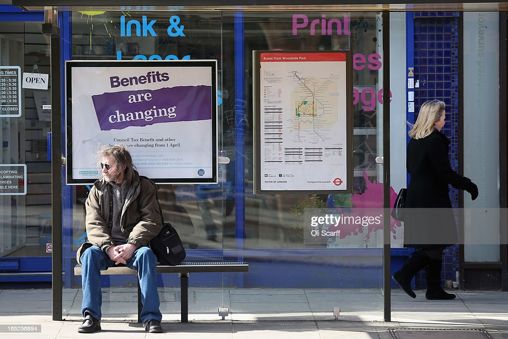 A man waits at a bus stop in North London in front of a poster informing of changes to the benefits and tax system that have come into force yesterday on April 2, 2013 in London, England. The widespread changes include a cut in housing benefit payments for working-age social housing tenants whose property is deemed larger than they need and council tax support payments being administered locally.