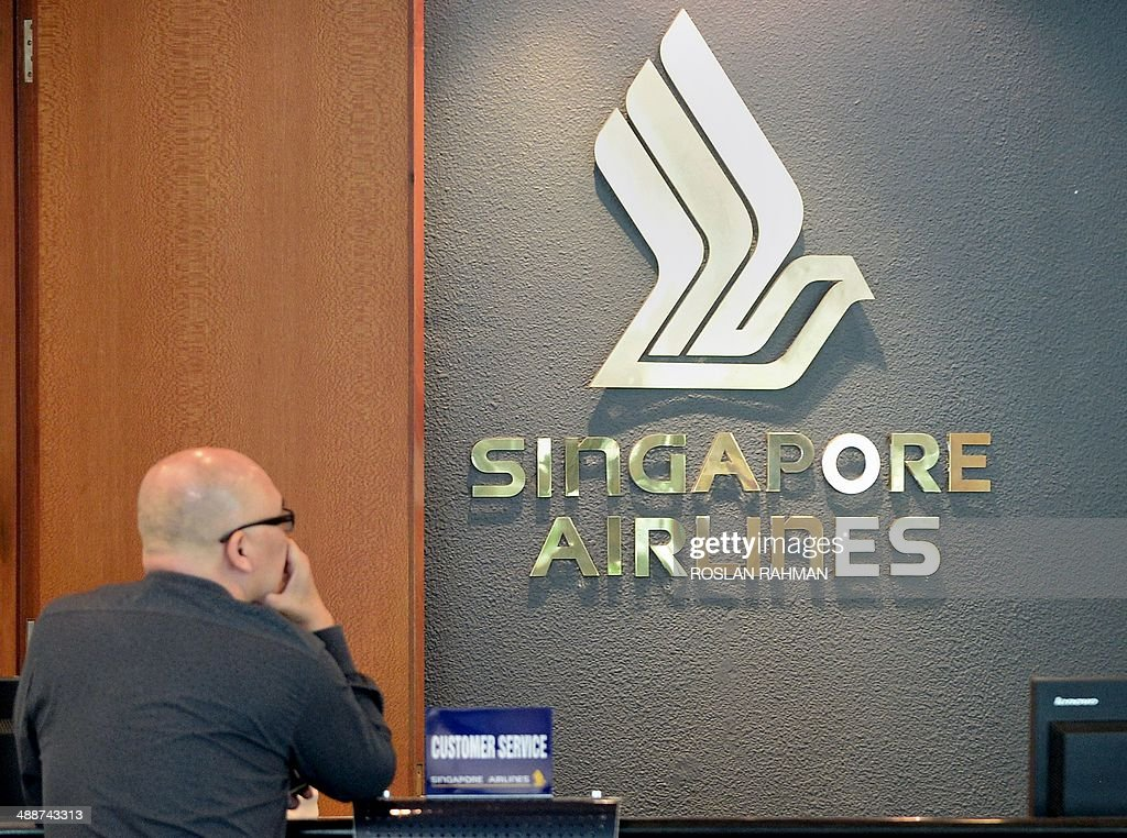 A man waits at the customer service counter of Singapore Airlines (SIA) at Changi International airport in Singapore on May 8, 2014. Singapore Airlines is to release its full-year earnings results on May 8 for the year 2013.