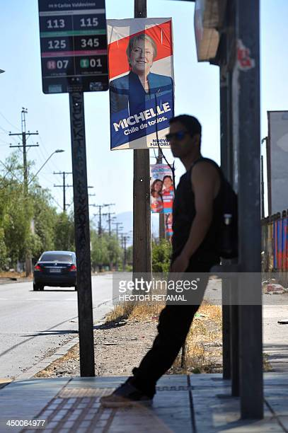 A man waits for a bus at a bus stop next to a billboard promoting the presidential candidate for the New Majority coalition Michelle Bachelet in...