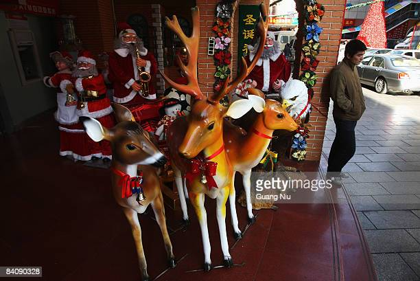 A man waits for a delivery job outside a Christmas decoration store on December 19 2008 in Beijing China A large number of Christmas decorations...