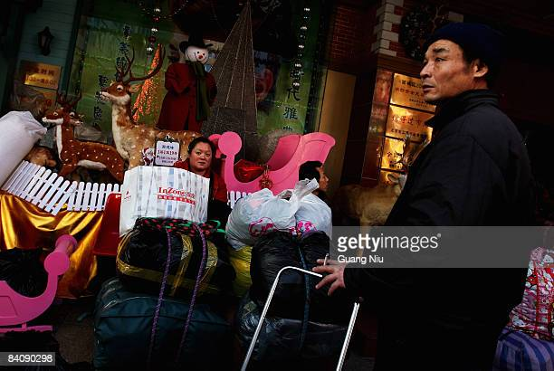 A man waits for a delivery outside a Christmas decoration store on December 19 2008 in Beijing China A large number of Christmas decorations destined...