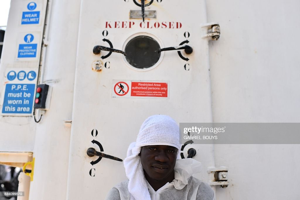 A man waits for a meal aboard the rescue ship 'Aquarius', on May 25, 2016 a day after a rescue operation of migrants and refugees off the Libyan coast. The Aquarius is a former North Atlantic fisheries protection ship now used by humanitarians SOS Mediterranee and Medecins Sans Frontieres (Doctors without Borders) which patrols to rescue migrants and refugees trying to reach Europe crossing the Mediterranean sea aboard rubber boats or old fishing boat. / AFP / GABRIEL